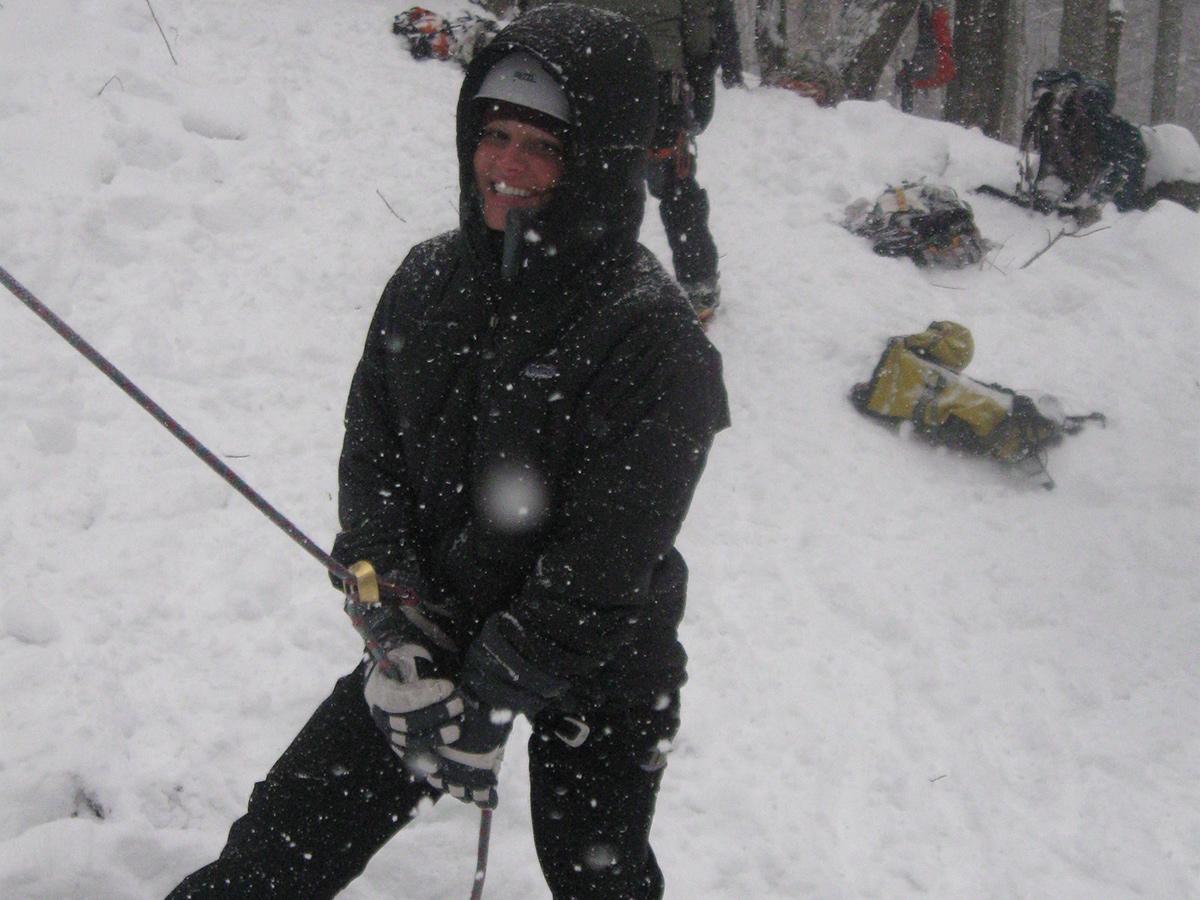A climber belaying an ice climb wearing a large puffy jacket.