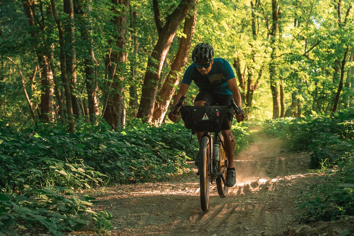A bikepacker riding along a trail