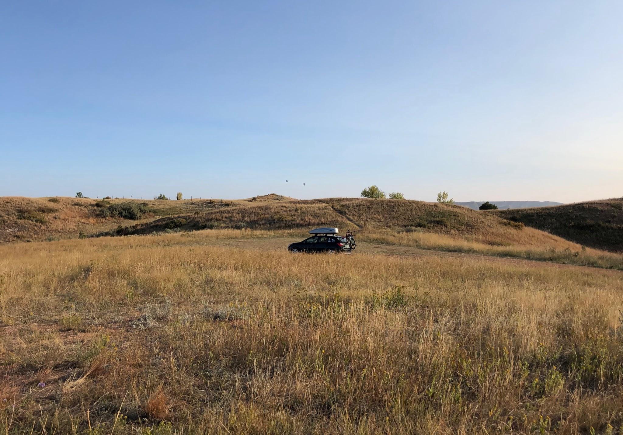 The author's Subaru Impreza parked amidst rolling fields